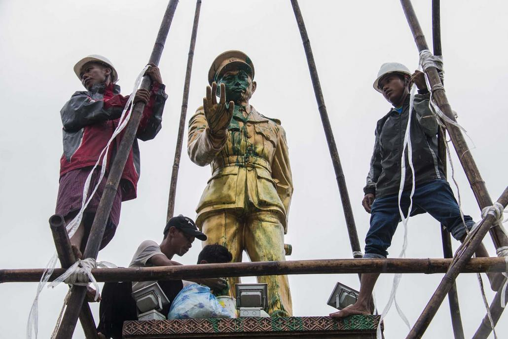 Workers clean a statue of Myanmar independence hero General Aung San in Myitkyina, the capital of Kachin State, after it was defaced with paint. (AFP)