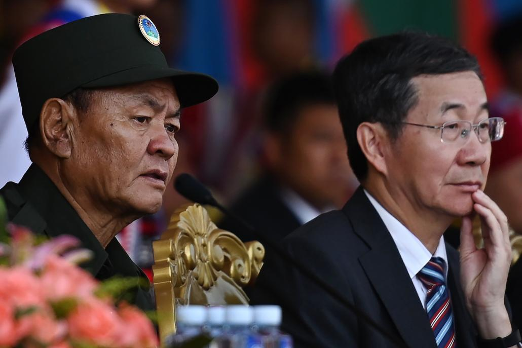 United Wa State Army leader Bao Youxiang (left) and China's Foreign Ministry's special envoy for Asian Affairs Sun Guoxiang watch a military parade, to commemorate 30 years of a ceasefire signed with the Myanmar military. (AFP)