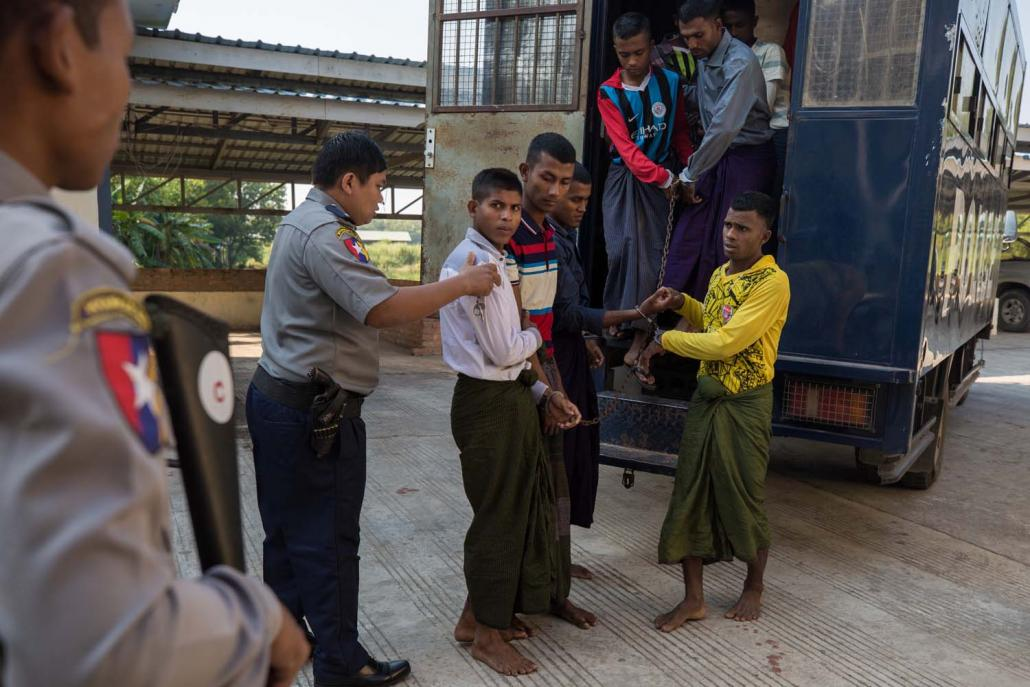 Rohingya detainees step out of a police van on arriving at Pathein Township Court on December 11. (AFP)