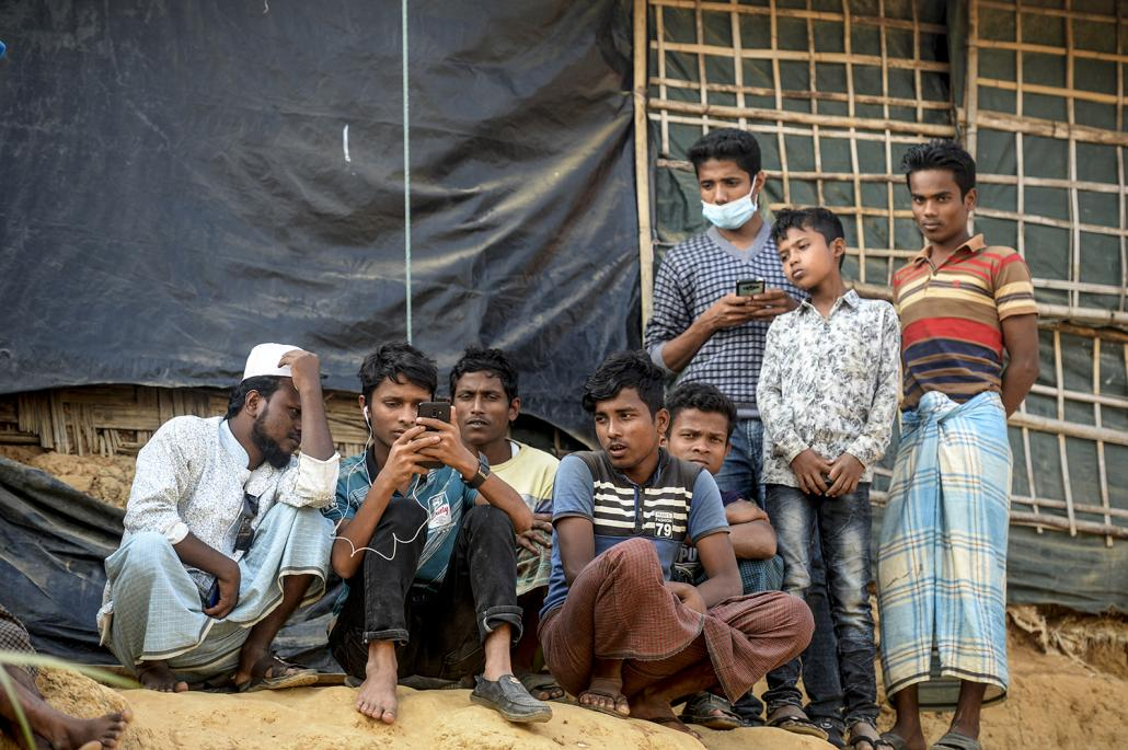Rohingya refugees watch on a mobile phone a live feed of State Counsellor Aung San Suu Kyi's appearance at the UN's International Court of Justice, in a refugee camp in Cox's Bazar, Bangladesh. (AFP)