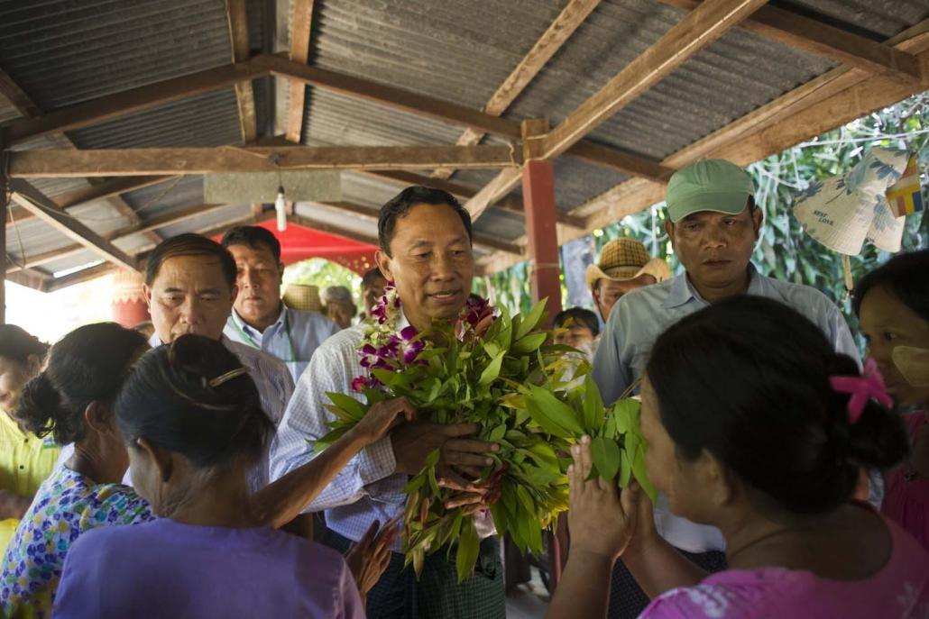 Shwe Mann receives flowers from supporters during an election campaign rally in Phyu Township in 2015. (AFP)