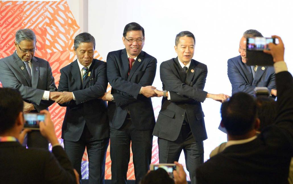 Minister for Planning and Finance U Kyaw Win (second left) holds hands with his counterparts from across the region during the ASEAN Economic Ministers' meeting in Manila on September 7, 2017. (AFP)