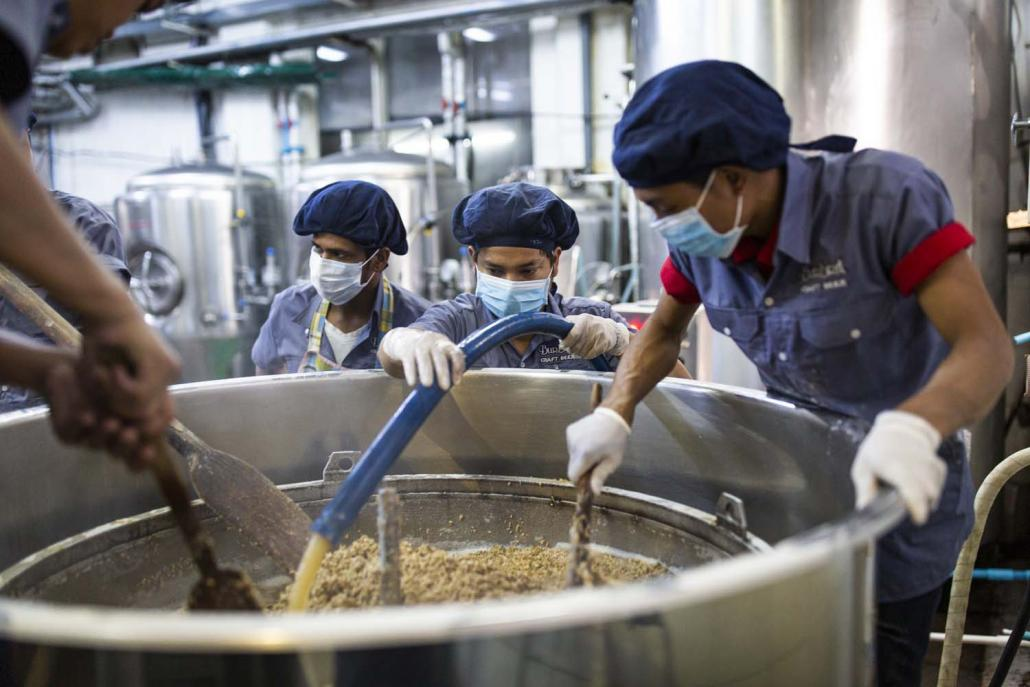 "Burbrit workers stir the mash – a mix of malted barley and hot water – in a mash tun. Known as ""mashing in"", it's the first step in the beermaking process. (Hkun Lat 