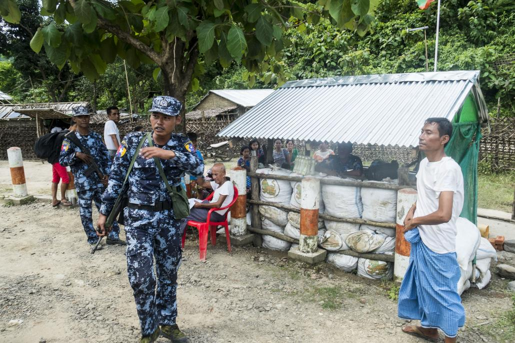 Border Guard Police officers stand guard at a village in Buthdaung Township. (Teza Hlaing | Frontier)