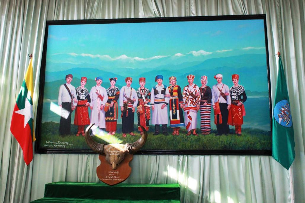 A painting representing six Kachin ethnic groups in their traditional dress hangs in the Myitkyina office of the Kachin National Association of Tradition and Culture. (Emily Fishbein | Frontier)