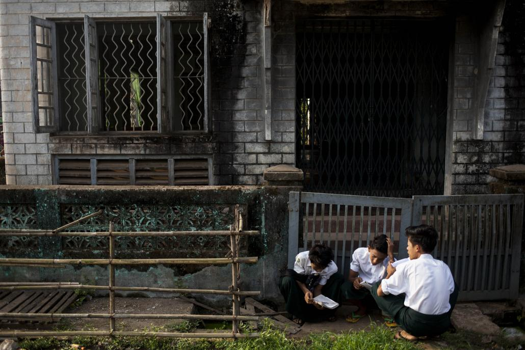 Students sit and study outside the Basic Education High School 8 in Bago. (Ann Wang / Frontier)