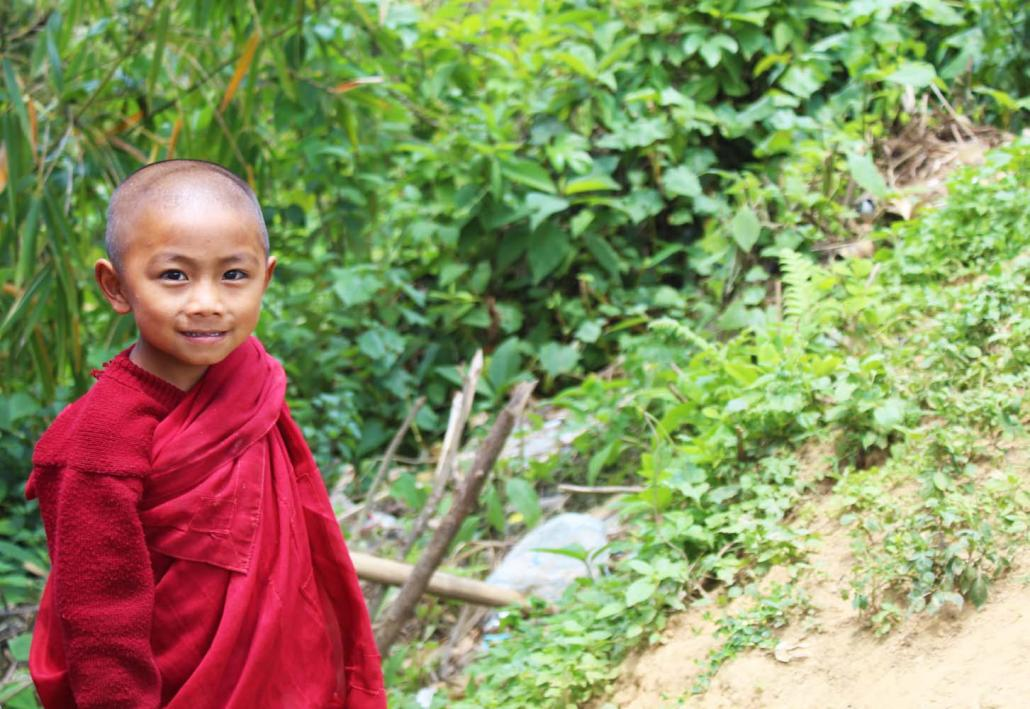 A novice Buddhist monk waits by the side of the road in the Naga SAZ. (Oliver Slow | Frontier)