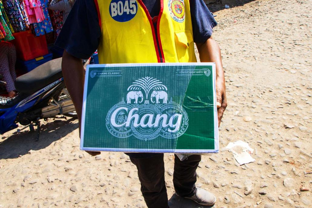 A worker carries a box of Thai-made Chang beer at Bayintnaung Market in Myawaddy Township. (Thuya Zaw | Frontier)
