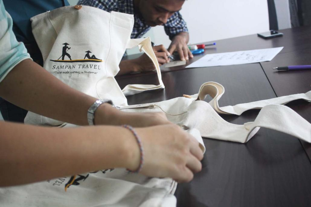 Sampan staff prepare bags for clients that contain souvenirs made from waste from the company's head office. (Supplied)
