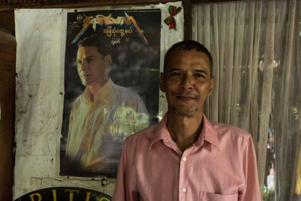 "Derek Millar at his home in North Okkalapa Township in front of a poster for his last album, ""Amye Sone Tweh Meh"" (Will Meet You Forever), released in 1998. (Teza Hlaing / Frontier)"
