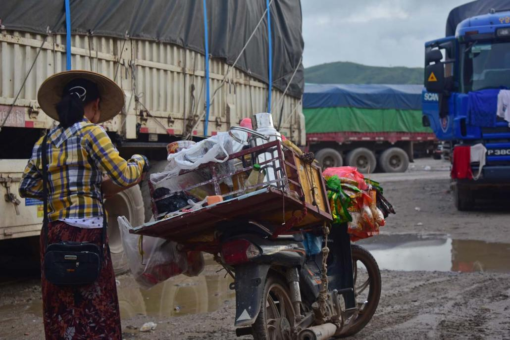 A migrant from Monywa sells snacks and drinks from the back of her motorbike at the 105 Mile trade zone south of Muse. (Kyaw Lin Htoon | Frontier)