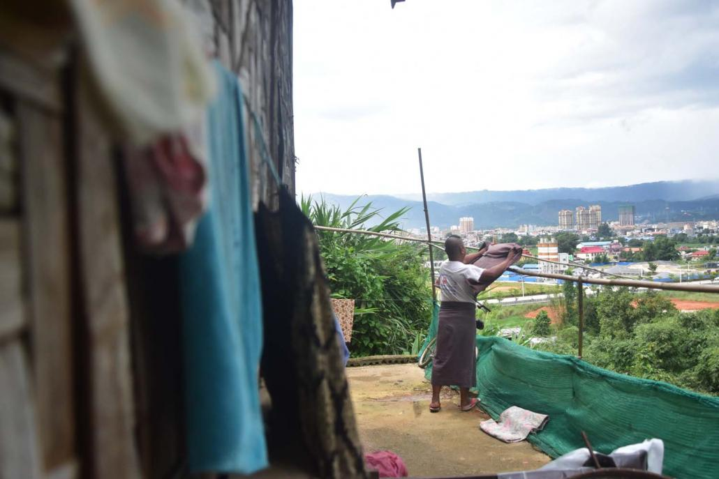 U Than, a migrant from Sagaing Region, hangs out a longyi to dry at his house in Muse's Christian ward, with the modern buildings of the Chinese city of Ruili visible in the background. (Kyaw Lin Htoon | Frontier)