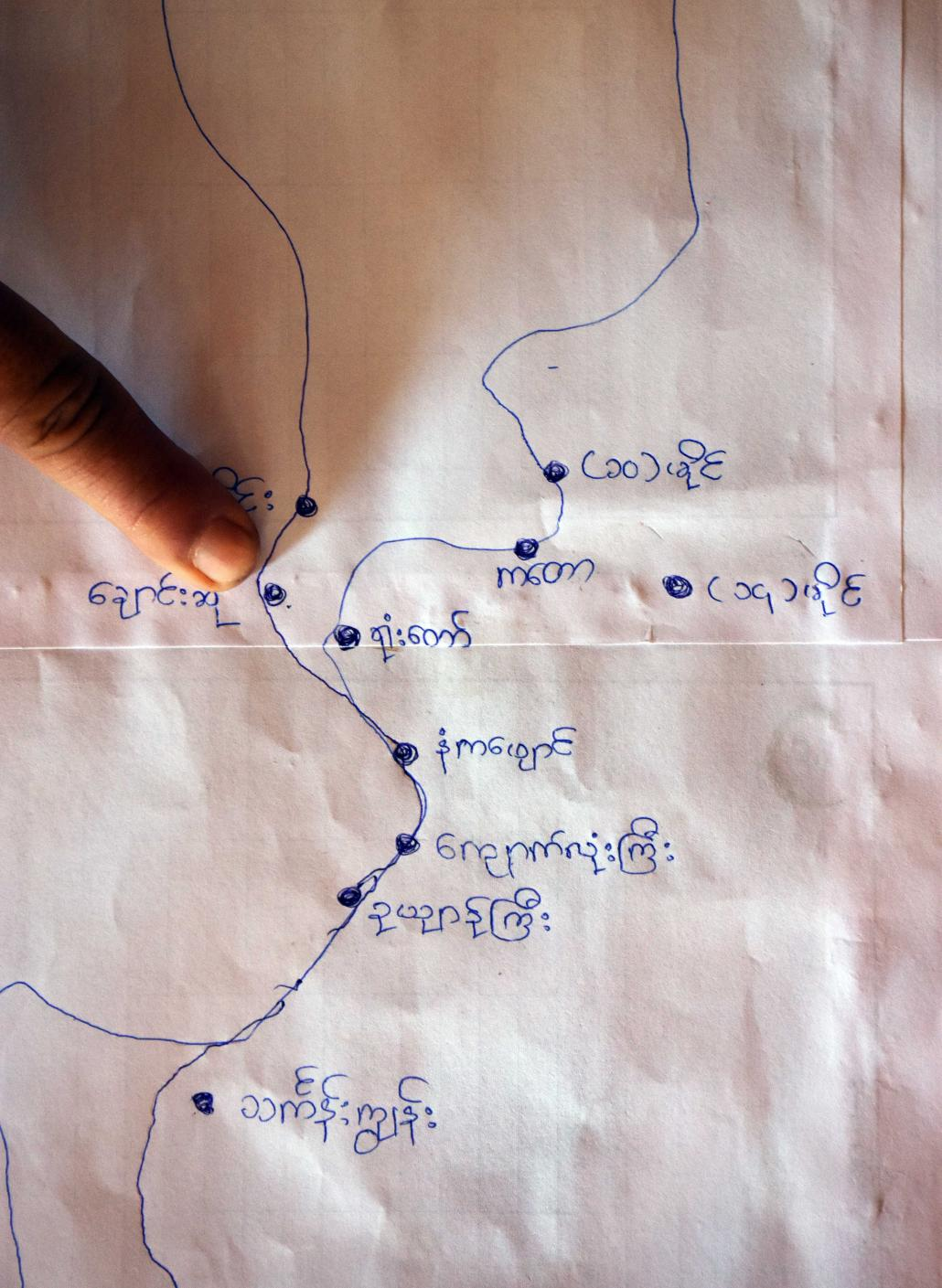 A local resident points to a home-made map showing 10 villages that could be affected if a national park is created along the Lenya River in Tanintharyi Region. (Steve Tickner | Frontier)
