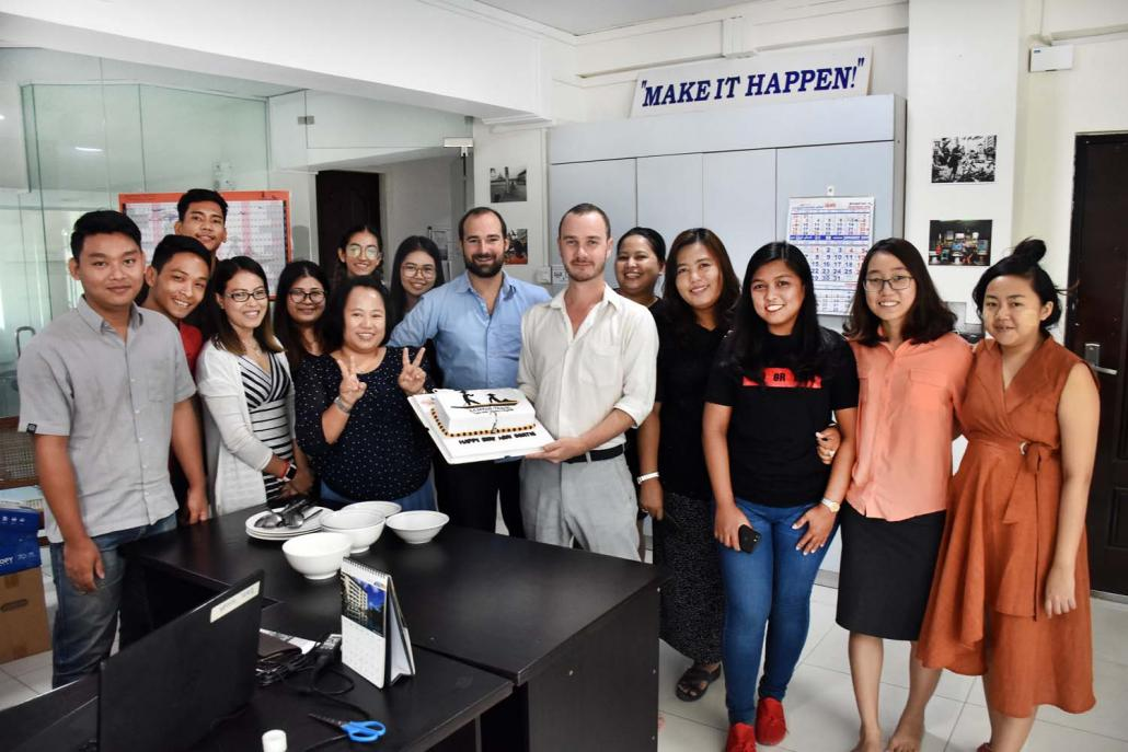 Mr Bertie Lawson, surrounded by members of the Sampan team, holds a cake with the Sampan Travel logo. (Steve Tickner | Frontier)