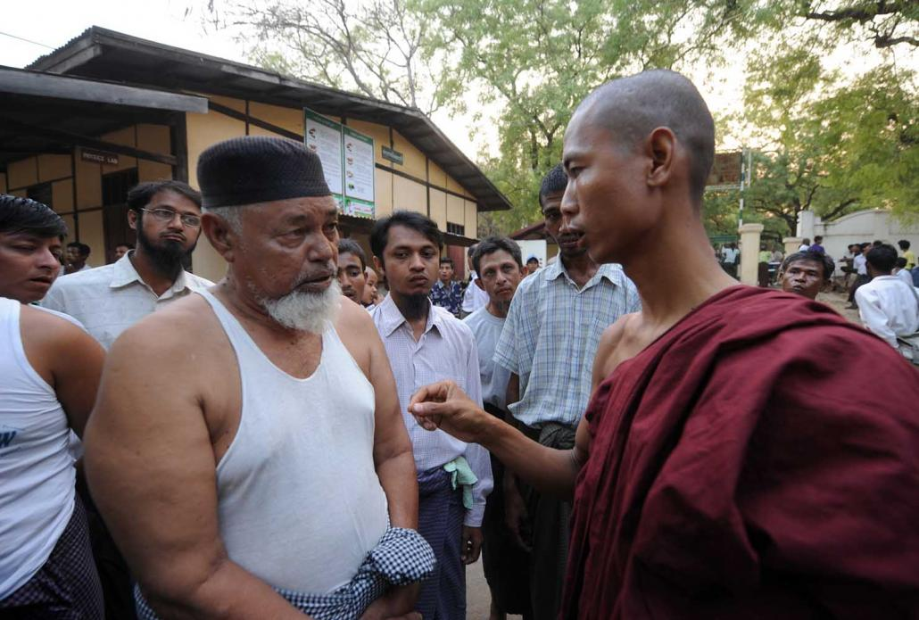A Buddhist monk and a Muslim man talk at a state school in Meiktila where Muslim residents had taken refuge following deadly communal conflict in March 2013. (Steve Tickner | Frontier)