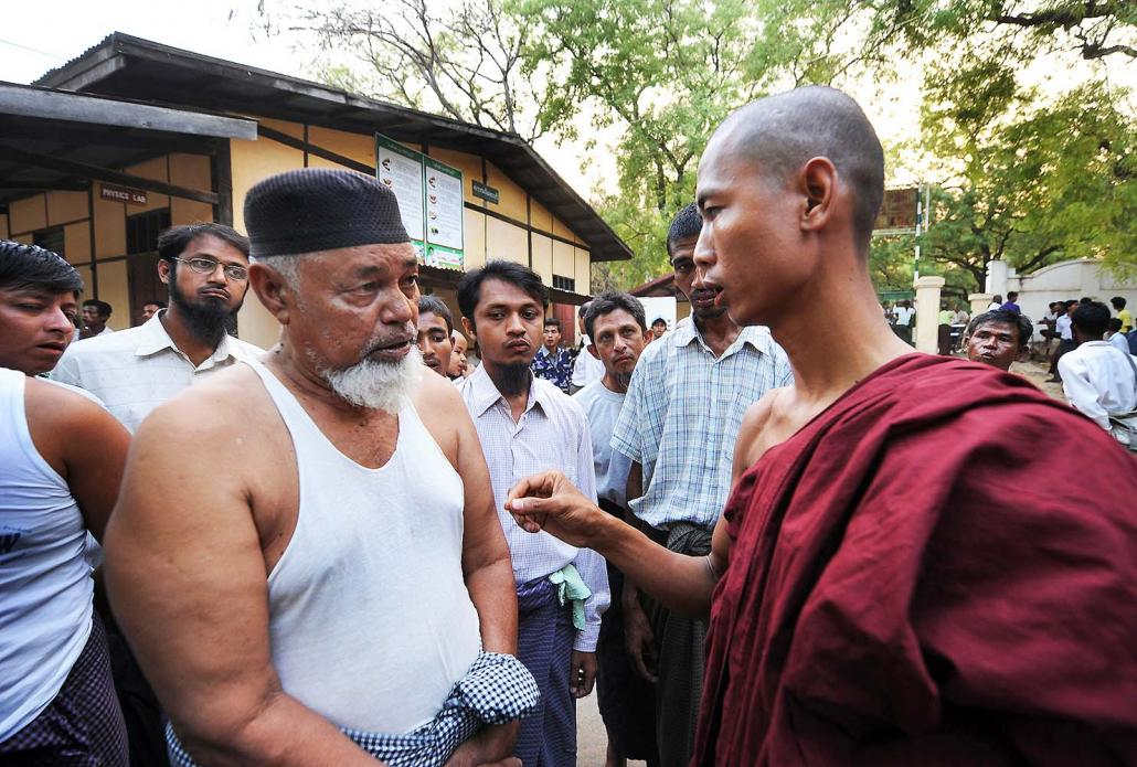 A Buddhist monk speaks with displaced Muslims taking refuge in a school in Meiktila in the aftermath of communal rioting in 2013. (Steve Tickner | Frontier)
