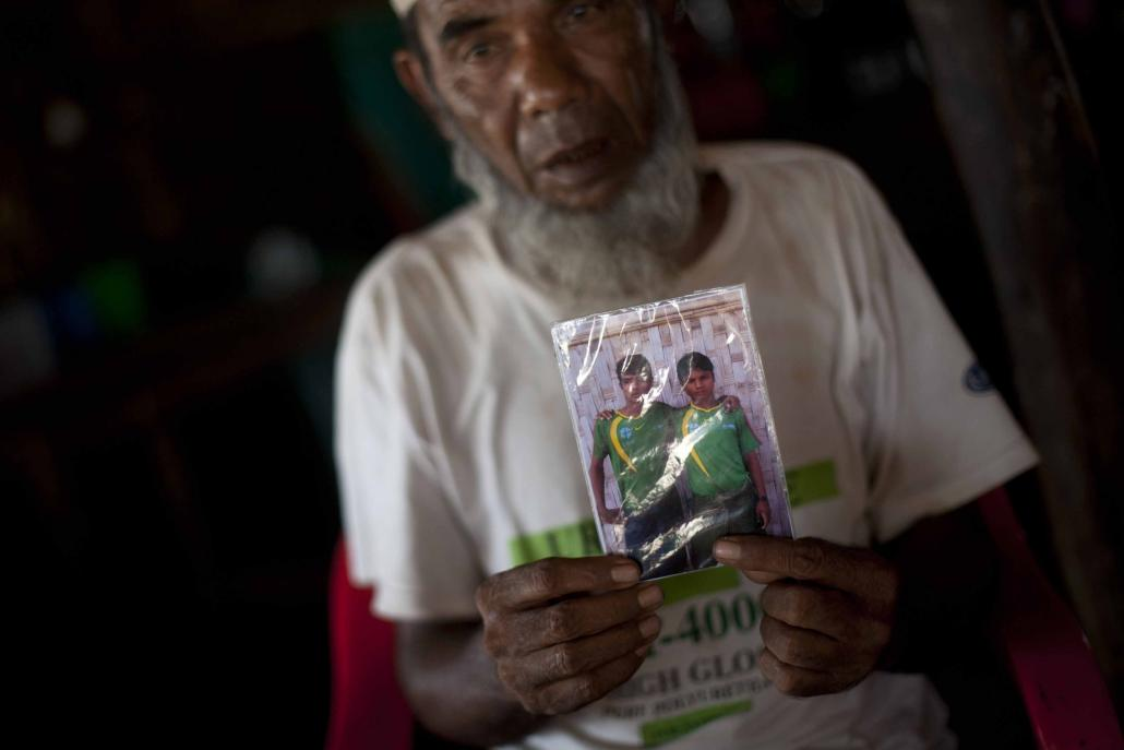 A Muslim man who identifies as Rohingya holds a picture of his son in May 2015. The man, a resident of an IDP camp in Sittwe, said his son was being held at a human trafficking camp in Malaysia. (AFP)