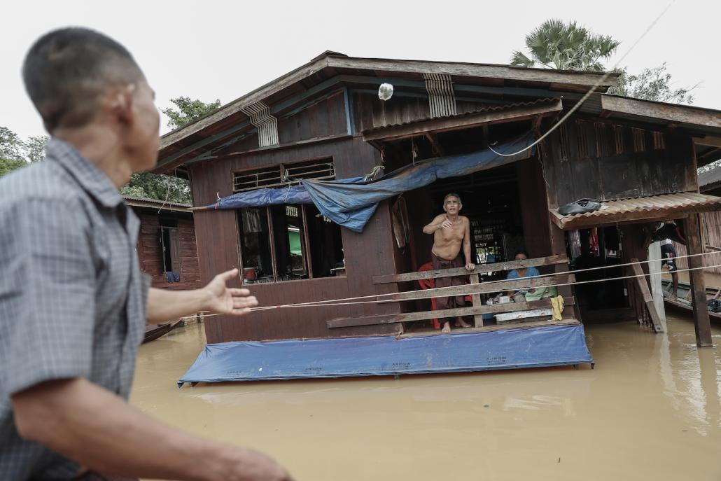 A resident gestures from the second-floor of his flooded home in Nga Pyay Ma village, in Mon State's Kyaikmayaw Township, on August 14. (Nyein Su Wai Kyaw Soe | Frontier)