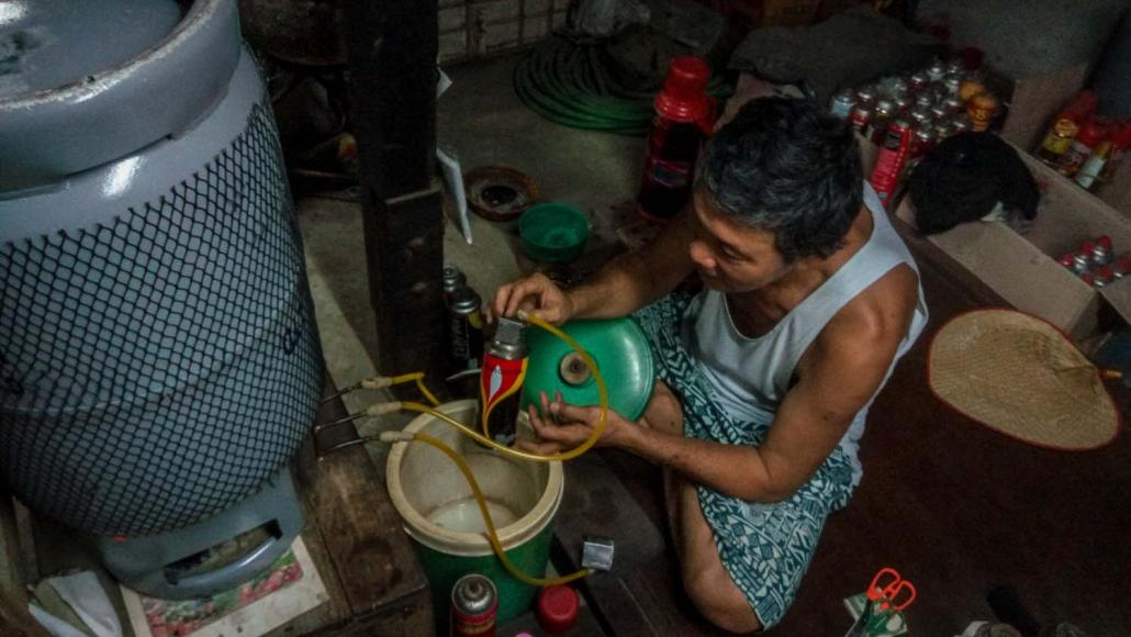 A worker at a gas shop fills up an LPG canister. (Kyaw Lin Htoon | Frontier)