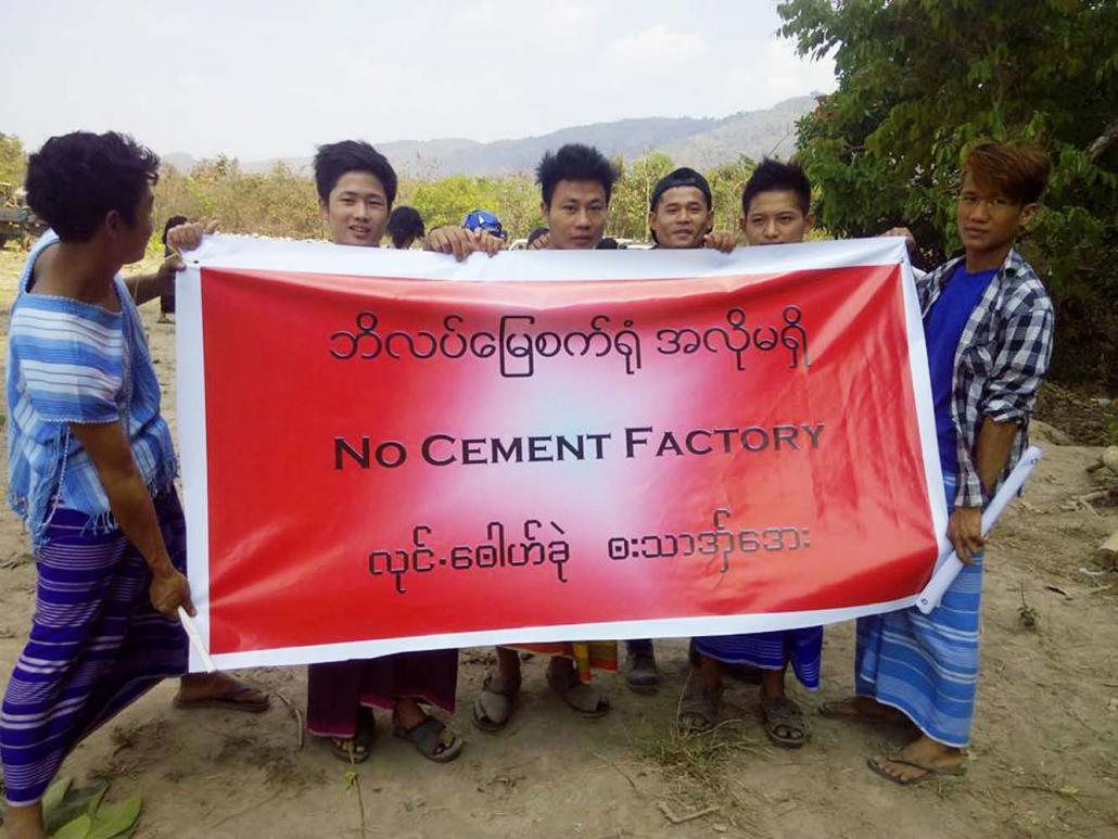 Mi Kayin residents hold a vinyl sign protesting against a proposed cement plant in the area. (KIC)