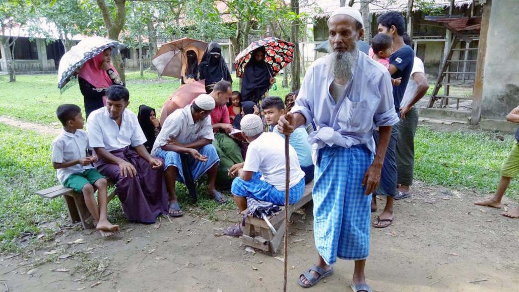 Rohingya villagers wait to be treated by a mobile clinic.