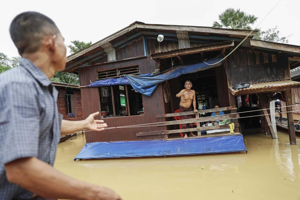 A resident of Nga Pyay Ma village in Kyaikmayaw Township gestures from the second floor of his flooded home on August 14. (Nyein Su Wai Kyaw Soe | Frontier)