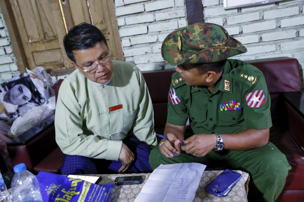 Ye Township administrator U Kan Win, discusses flood relief activities with a Tatmadaw officer on August 12. (Nyein Su Wai Kyaw Soe | Frontier)