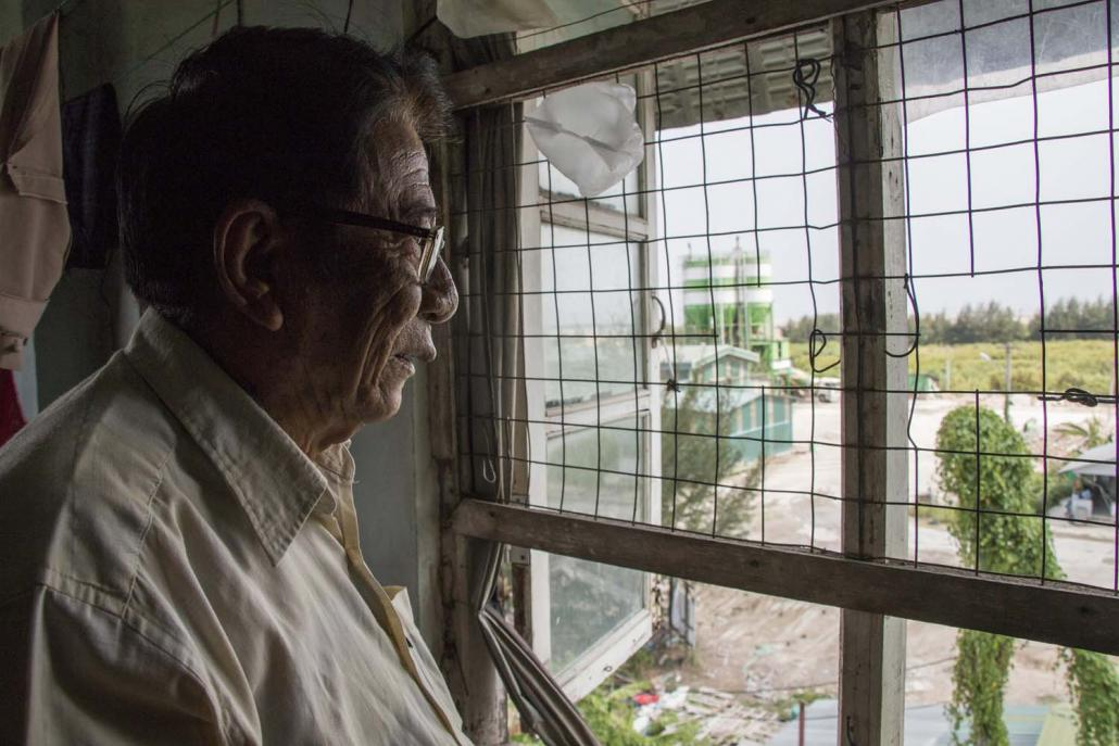 U Maung Maung Lwin, 79, looks out his window towards the Tet Lann Concrete factory. (Nyein Su Wai Kyaw Soe | Frontier)