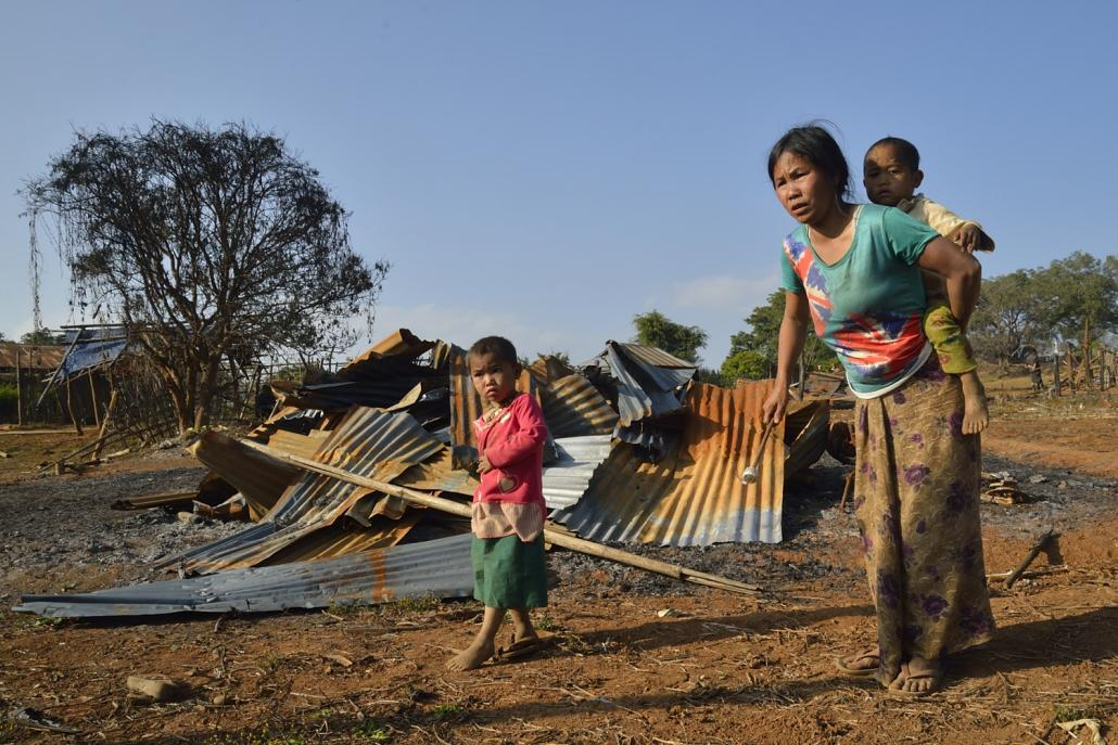 A woman and her two children in the village of Pankan, Kutkai township, in front of their flattened home. (Niels Larsen / Frontier)