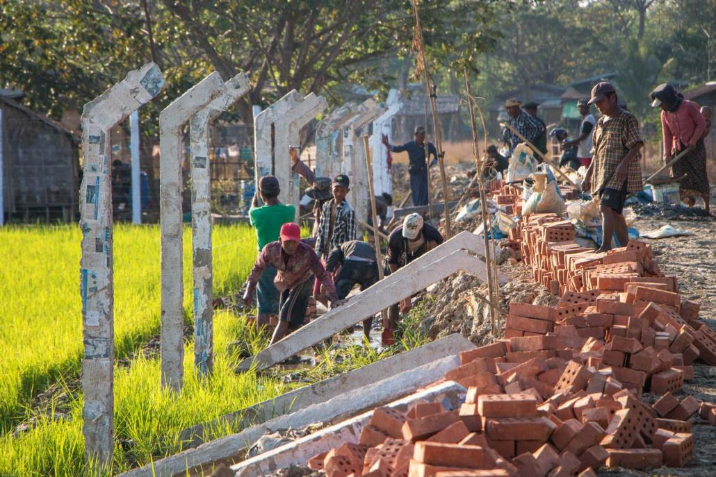 Workers build a fence to enclose more than 200 acres of farmland in South Dagon Township on February 4. (Thuya Zaw | Frontier)