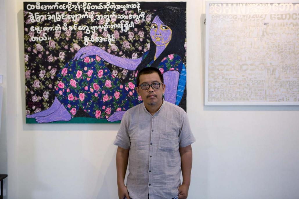 "Htein Lin before a painting from his ""Skirting the Issue"" exhibition, which tackled misogynist taboos with canvases made from women's longyis. (Thuya Zaw 
