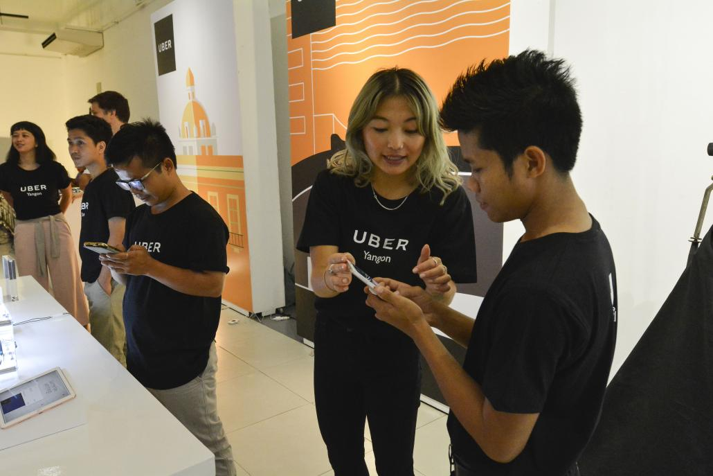 An Uber staffer explains the service at the company's launch in Yangon on May 11. (Teza Hlaing | Frontier)