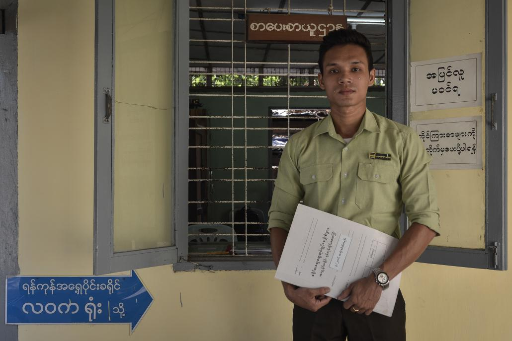 A civil servant stands outside the Eastern Yangon General Administration Department office in Thingangyun Township. (Teza Hlaing / Frontier)