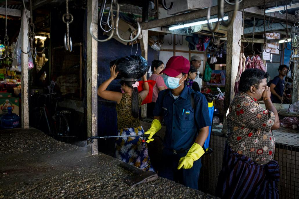 A member of Yangon City Development Committee disinfects Pazundaung market on March 21 as part of efforts to prevent the spread of COVID-19 in Yangon. (Hkun Lat I Frontier)