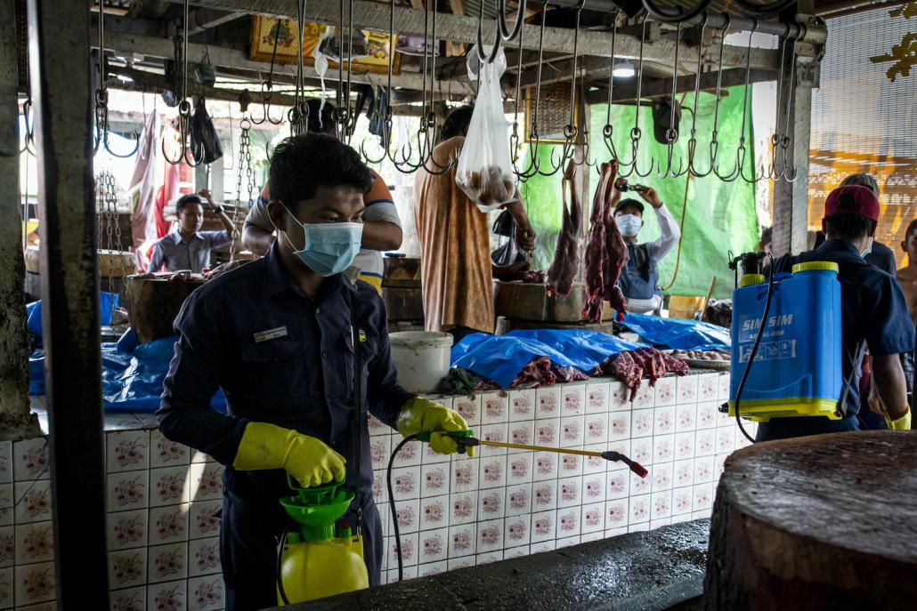 A Yangon City Development Committee official disinfects Pazundaung market to help prevent the spread of COVID-19 in Yangon on March 21. (Hkun Lat I Frontier)