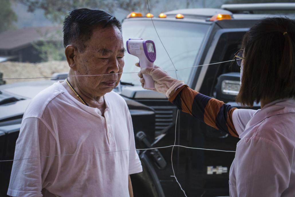 Kachin Independence Organisation leader General N'Ban La has his temperature checked at the entrance to Laiza, the group's headquarters on the Myanmar-China border, on March 31. (Naw Seng I Frontier)
