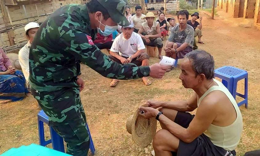 A soldier from the Shan State Army-South, armed wing of the Restoration Council of Shan State, checks a person for fever, one of the symptoms of COVID-19. (Supplied)