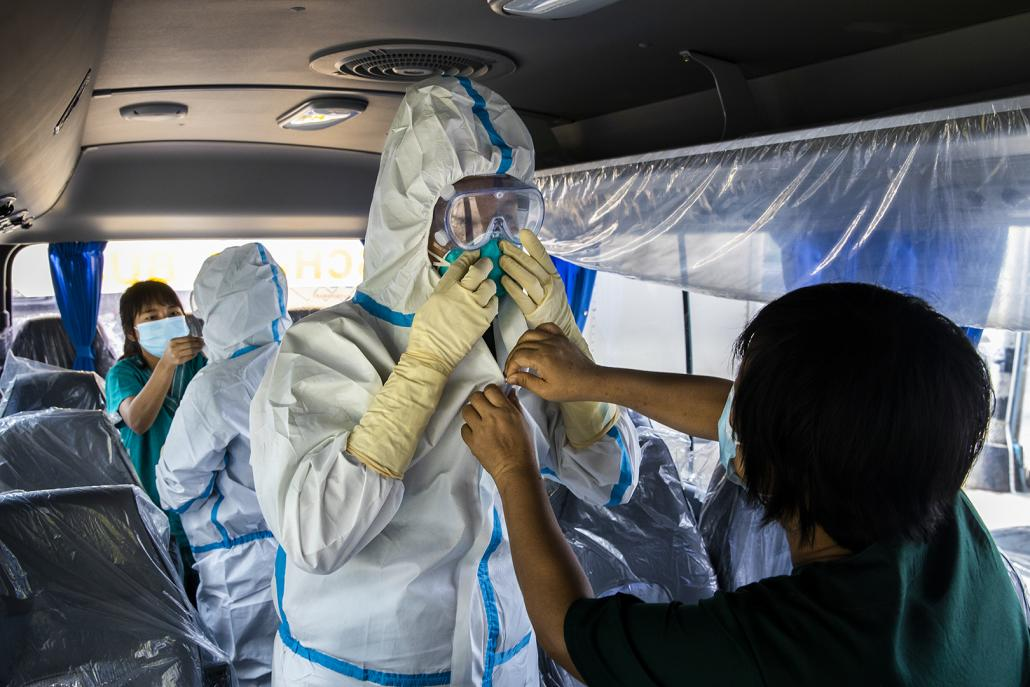 "Medical workers put on personal protective equipment before testing for COVID-19 among guests at a ""quarantine hotel"" in Yangon May 22. (Hkun Lat 