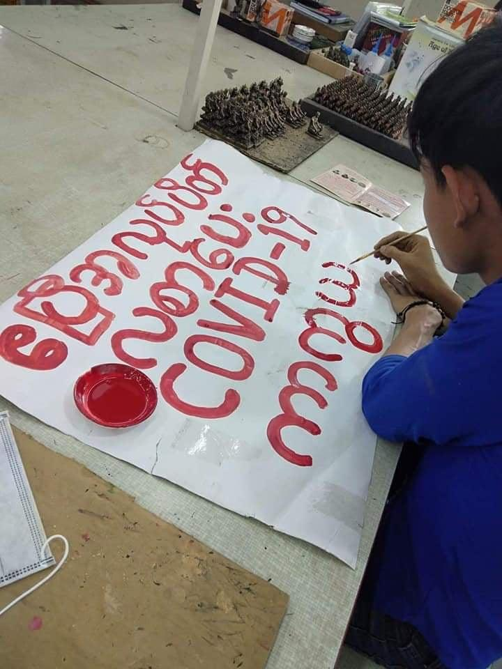 A worker paints a sign calling for factories to be shut in April and workers to receive full pay in order to prevent the spread of the coronavirus. (FGWM | Supplied)