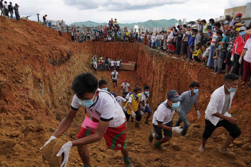 Volunteers bury bodies of miners in a mass grave while relatives look on during a funeral ceremony near Hpakant, Kachin State on July 3. (AFP)