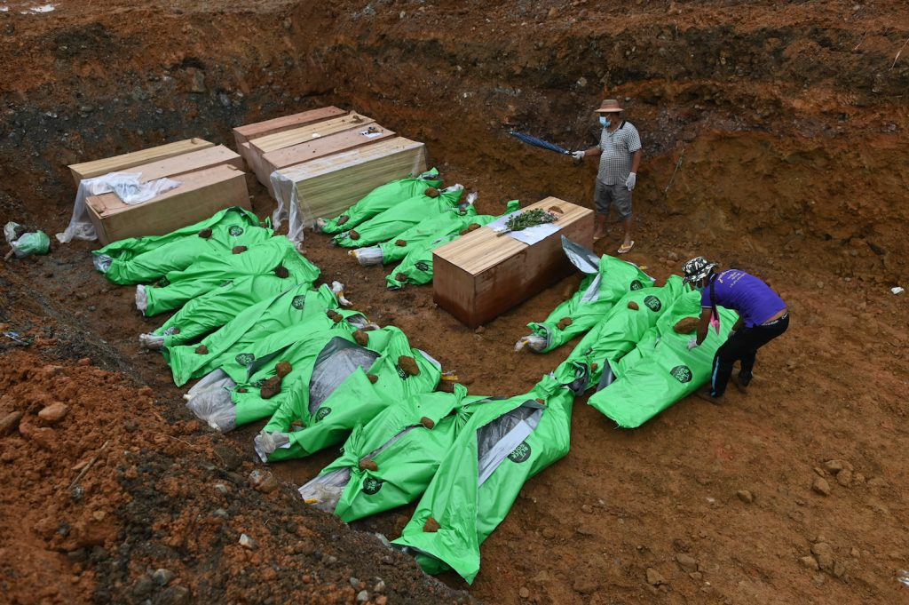 The bodies of miners in wooden coffins and wrapped up in bags are placed in a mass grave before being buried, on July 4. (AFP)