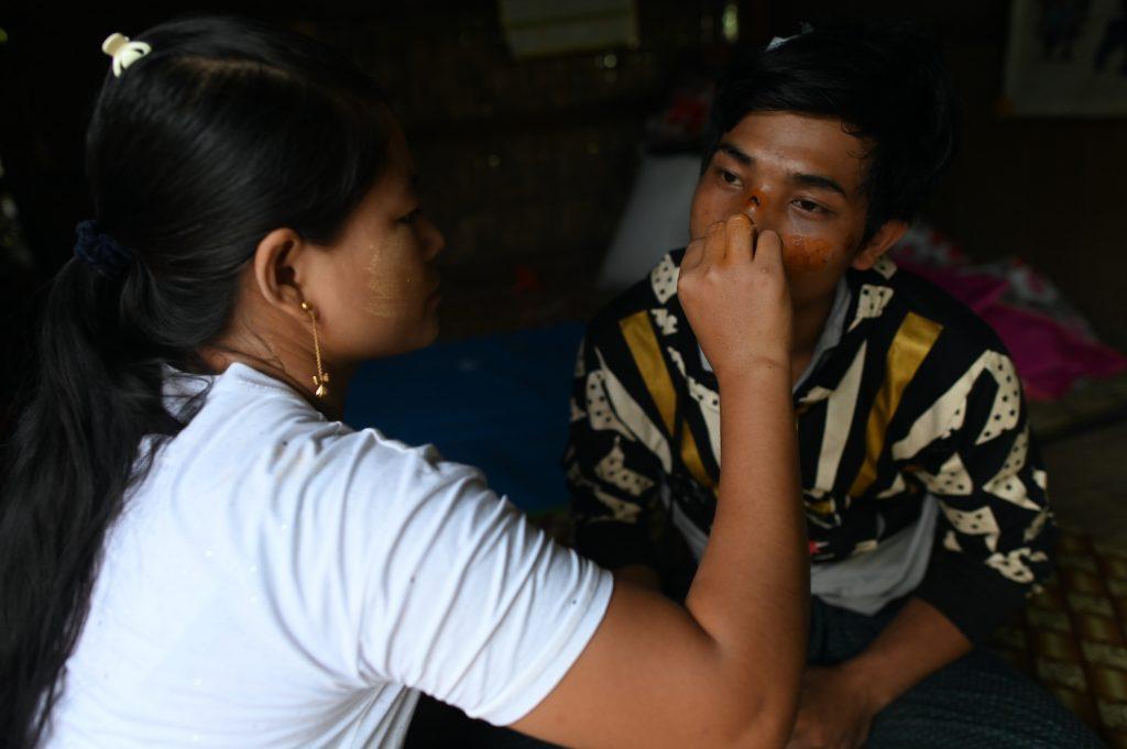 Ma Pan Ei Phyu treats her husband Sai Ko, who survived the deadly landslide. (AFP)