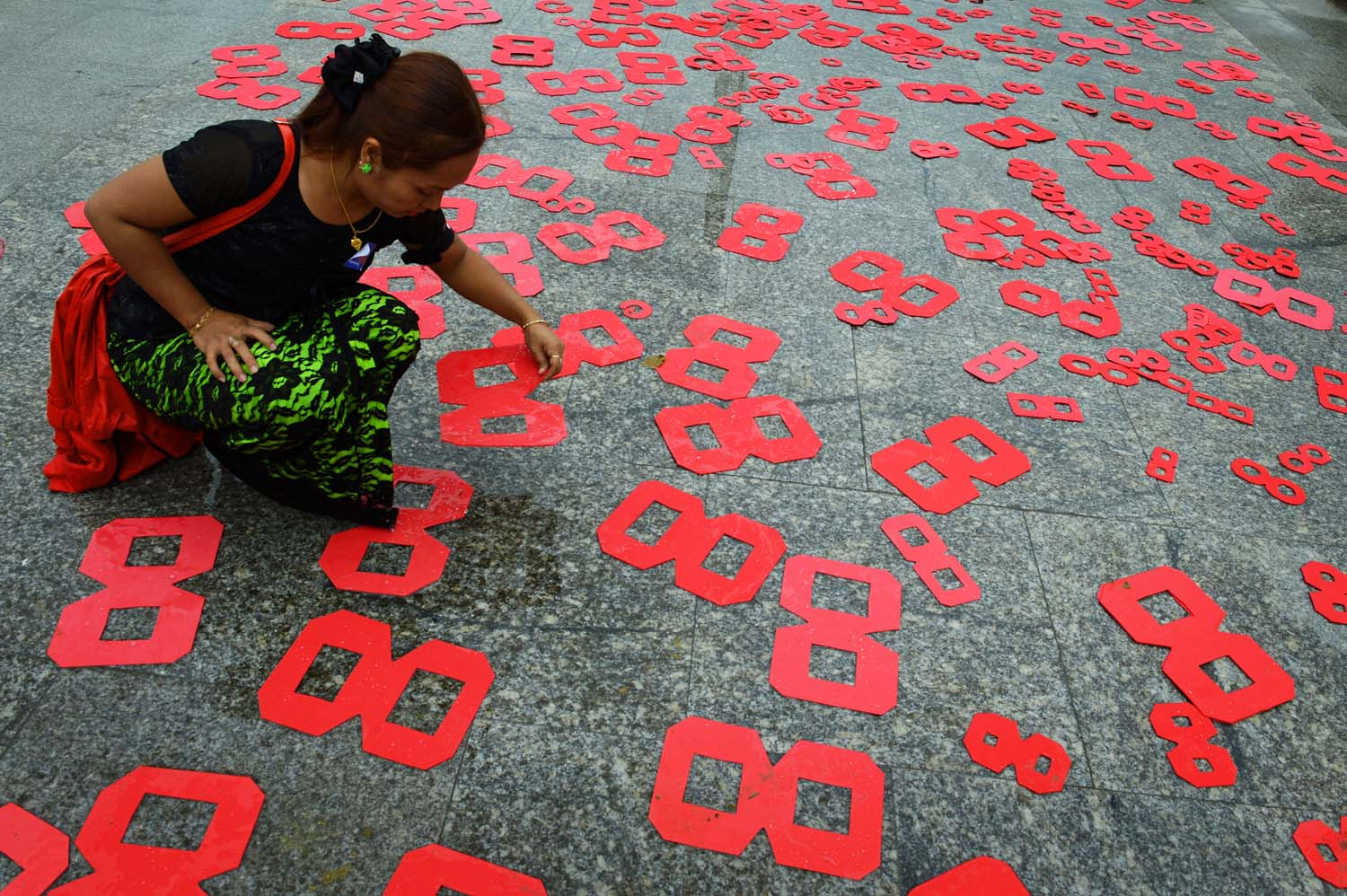 An activist places cutouts on the ground in Mahabandoola Park in Yangon on August 8, 2016 to mark the 28th anniversary of a general strike, one of the key events of the 1988 uprising. (AFP)