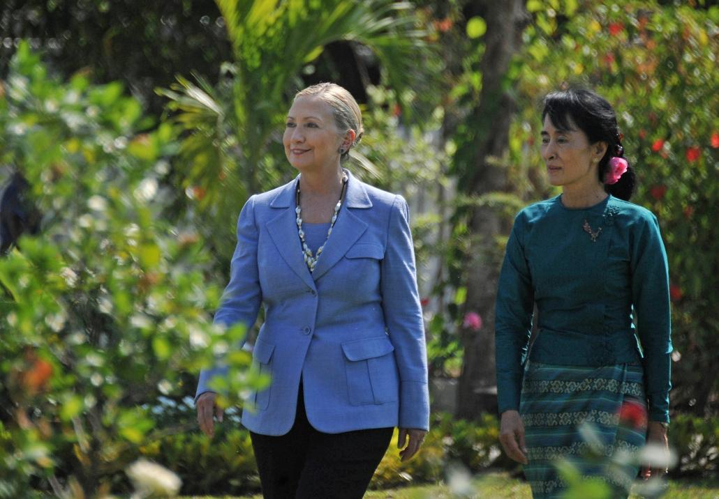 Aung San Suu Kyi and visiting Hillary Clinton tour the grounds of Suu Kyi's Yangon residence on December 2, 2011. (Soe Than Win / AFP)