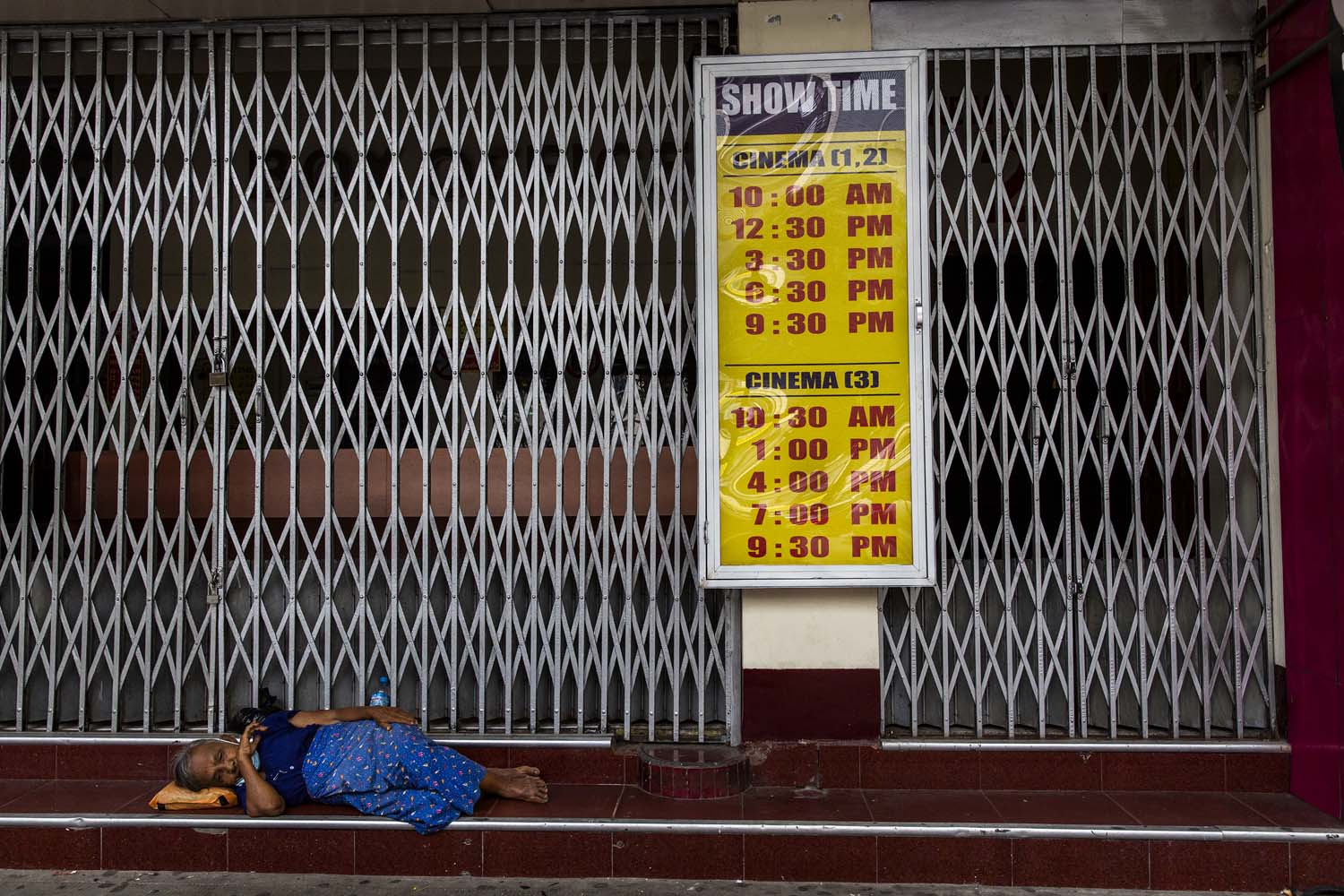 A woman rests in front of the shuttered Shae Saung Cinema on Yangon's Sule Pagoda Road on July 27. (Hkun Lat I Frontier)