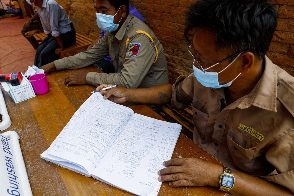 Security guards at the Dhammayangyi temple log the details of visitors undergoing health checks on June 22. (Nyein Su Wai Kyaw Soe | Frontier)