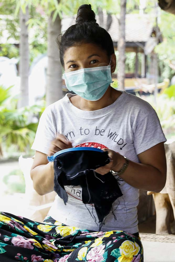 Ma Thandar earns a reduced daily wage of K3,500 at Bagan House Lacquerware sewing face masks featuring traditional floral designs. (Nyein Su Wai Kyaw Soe | Frontier)