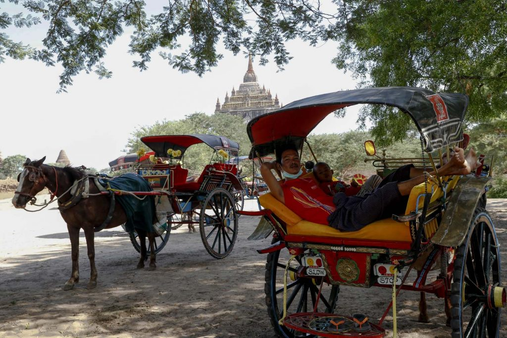 An under-employed horsedrawn carriage driver lounges at the Thatbyinnyu temple on June 23. (Nyein Su Wai Kyaw Soe | Frontier)