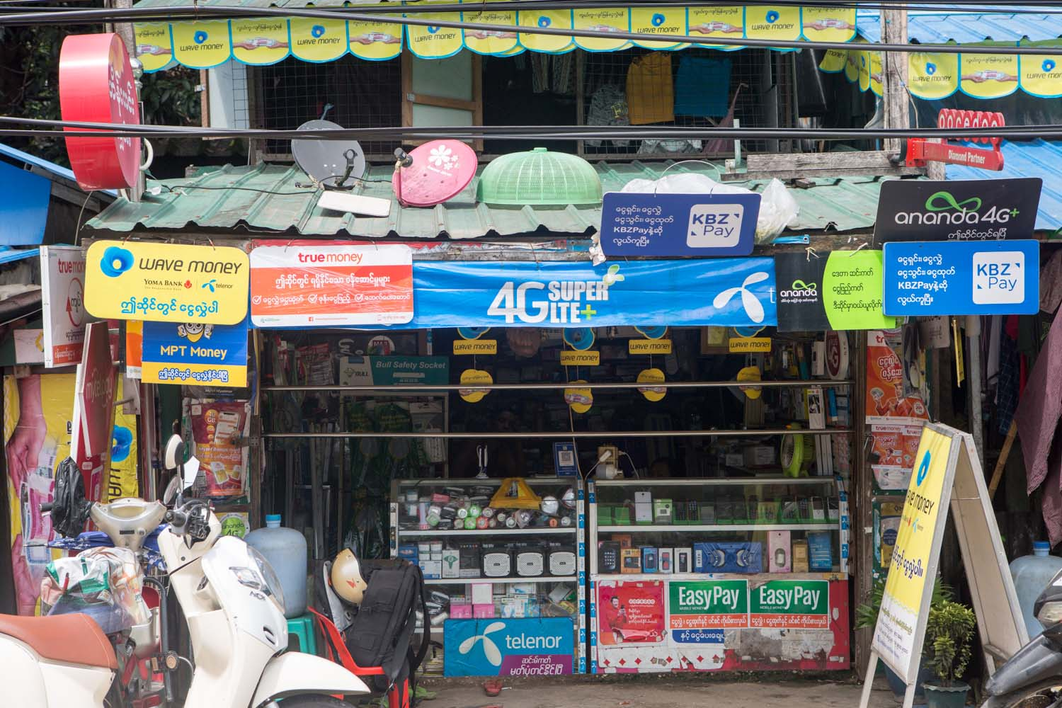 A shop in Yangon's Insein Township adorned with mobile money signs on July 8. (Thuya Zaw | Frontier)