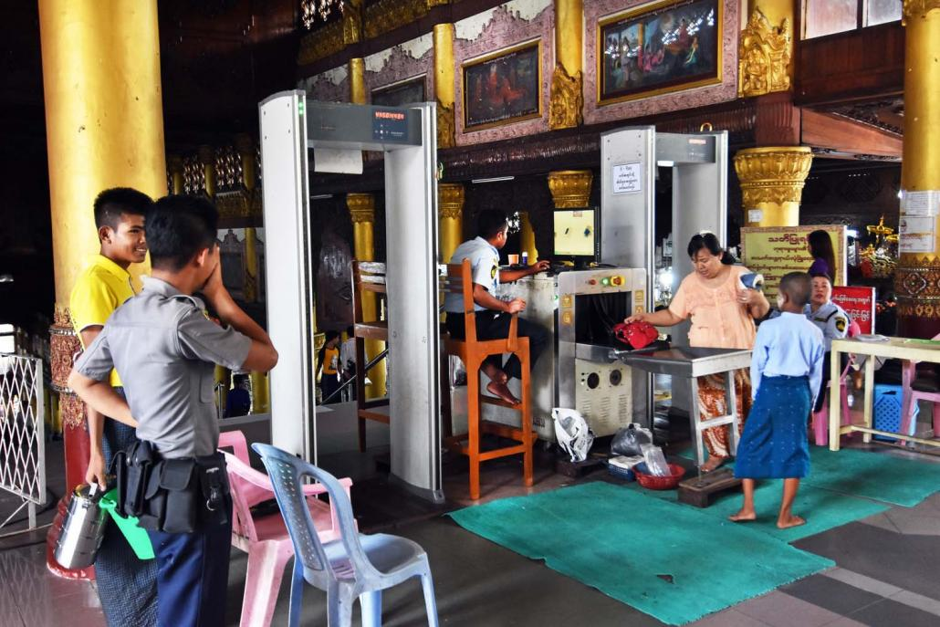 Security guards screen bags and visitors at the entrance to Shwedagon Pagoda in Yangon. (Steve Tickner | Frontier)